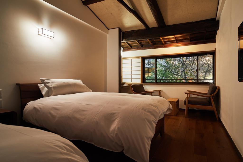 二階主寝室 天井は梁を出し空間を広げました。窓からは高瀬川沿いの桜の木を一人占め。窓のサイズにもこだわりました。